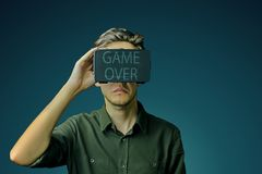 Man uses VR. Young man in a shirt uses virtual reality glasses with the inscription `game over` on them in front of a dark green eden background stock photos