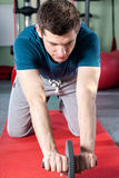Man using abdominal roller Royalty Free Stock Photos