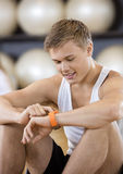 Man Using Activity Tracker While Sitting In Gym Stock Photo