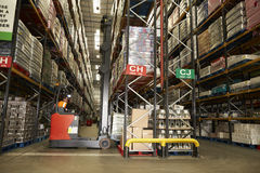 Man using aisle truck in a distribution warehouse, back view Royalty Free Stock Image