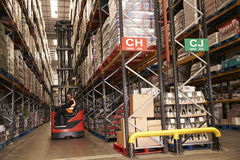 Man using aisle truck in a distribution warehouse, side view Royalty Free Stock Photo