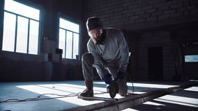 Man using angle grinder. Bearded man in protective glasses working in hangar and cutting metal rod with angle grinder Royalty Free Stock Photo
