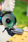 Man using angle grinder to cut metal bar Stock Photos