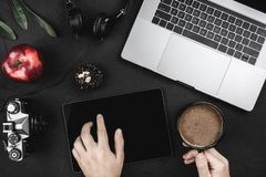 Man using app with digital tablet, sitting at cafe. Top view of laptop and headphones, red apple on a black table royalty free stock images