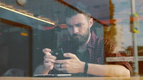 Man using app on smartphone in cafe. Shot through window stock footage