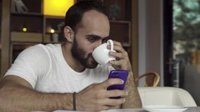 Man using app on smartphone drinking coffee, texting on mobile phone