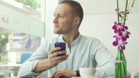 Man using app on smartphone drinking coffee, texting on mobile phone. Man using app on smartphone drinking coffee smiling and texting on mobile phone stock video footage
