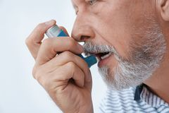 Man using asthma inhaler on white background. Closeup royalty free stock photography