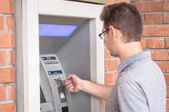 Man using ATM bank machine Royalty Free Stock Images