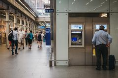 Man using an ATM inside St. Pancras station,London, UK. royalty free stock photography