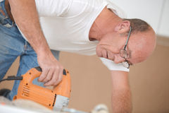 Man using band saw Stock Images