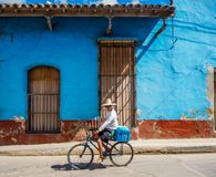 Man using bike for transport in Trinidad. Riding in by an eroded blue house Royalty Free Stock Images
