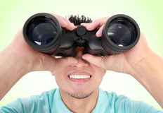 Man Using Binocular. Portrait Of A Young Man With Binocular Over A Green Background royalty free stock photography
