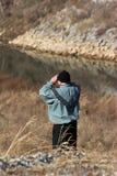 Man using binoculars outdoors. Rear view of man using binoculars on hillside Royalty Free Stock Images