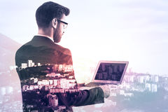 Man using blank laptop. Side view of businessman using laptop with blank screen on creative city background. Double exposure Stock Photo