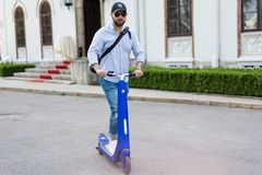 Man using blue electric scooter in the park royalty free stock image