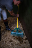 Man using broom to clean the stable. Mature man using broom to clean the stable Stock Photography
