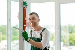 Man using a bubble level. To inspect how perpendicular a unit is. Quality window installation made by handsome worker royalty free stock photo