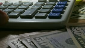 Man using calculator for business calculations. Close up of hand, money and calculator stock video footage