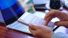 Man using calculator at desk, close up. Man using calculator at desk, backlit by sunshine through window, close up Stock Photography