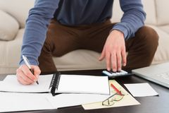 Man using calculator and taking notes Royalty Free Stock Photo