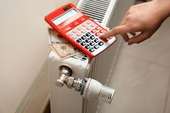 Man using calculator to count heating expenses. On radiator indoors royalty free stock photo