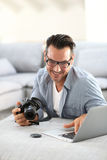 Man using camera and laptop Stock Photography