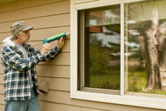 Man using a caulking gun Stock Image