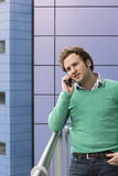 Man Using Cell Phone On Balcony. Handsome young man using cell phone on balcony Royalty Free Stock Photo