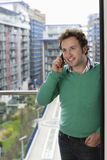 Man Using Cell Phone On Balcony. Happy young man using cell phone on balcony Royalty Free Stock Images