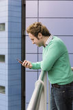 Man Using Cell Phone On Balcony. Side view of young man using cell phone on balcony Royalty Free Stock Photo