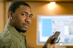 Man using cell phone and computer. African American young adult text messaging on cell phone Royalty Free Stock Images