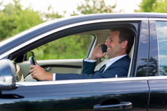 Man using cell phone while driving. Stock Image