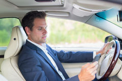 Man using cell phone while driving Stock Images