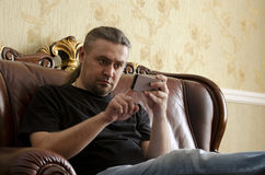 Man using cell phone. Sitting on the sofa in the room Stock Image
