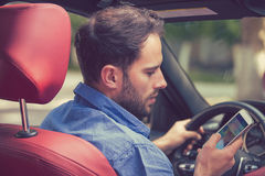 Man using cell phone texting while driving. Reckless driver. Man using cell phone texting while driving. Risky, reckless driver concept Stock Images