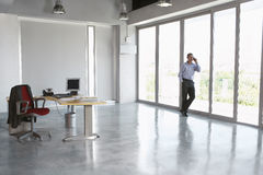 Man Using Cellphone Against Glass Wall In Empty Office. Full length of a male executive using cellphone against glass wall in empty office Stock Photo