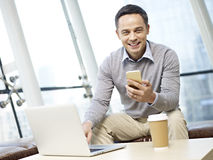Man using cellphone and laptop Royalty Free Stock Photo