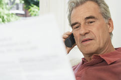 Man Using Cellphone And Looking At Bill Stock Images