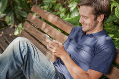 Man using a cellphone in the park Stock Photos