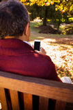 Man using cellphone while relaxing on bench royalty free stock photo