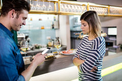 Man using cellphone while sad girlfriend standing by him royalty free stock images