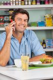 Man Using Cellphone At Table In Supermarket Royalty Free Stock Photos