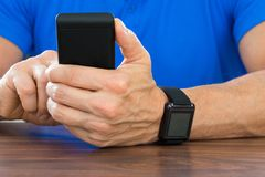 Man using cellphone and wearing smartwatch Royalty Free Stock Photo