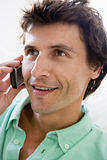 Man using cellular phone and smiling Stock Photography