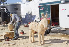 Man using Chainsaw to carve a donkey wood carving Royalty Free Stock Images