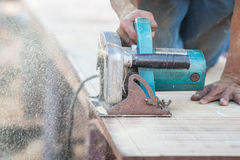 Man using a circular saw to cut the wood Stock Image