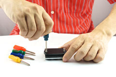 Man using colorful screwdriver for repair. Man using screwdriver with screw for minor repair with white background Royalty Free Stock Images
