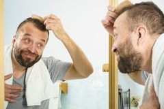 Man using comb in bathroom. Adult man standing in front of the bathroom mirror brushing his short hair using comb. Guy investigating his receding hairline royalty free stock image