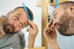 Man using comb in bathroom. Adult man standing in front of the bathroom mirror brushing his short hair using comb. Guy investigating his receding hairline royalty free stock photography